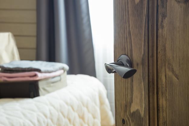 Otwórz drewniane drzwi i widok na sypialnię. otwórz walizkę z ubraniami.