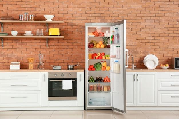 Otwórz dużą lodówkę z produktami we wnętrzu kuchni