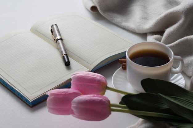 Otwórz dziennik, długopis, kubek z gorącą kawą, szalik, tulipany na białej powierzchni. koncepcja wiosny. leżał płasko, widok z góry