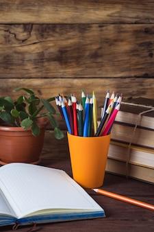Otwórz dziennik, stos książek, kolorowe kredki w plastikowym szkle, kwiat w doniczce na drewnianym tle