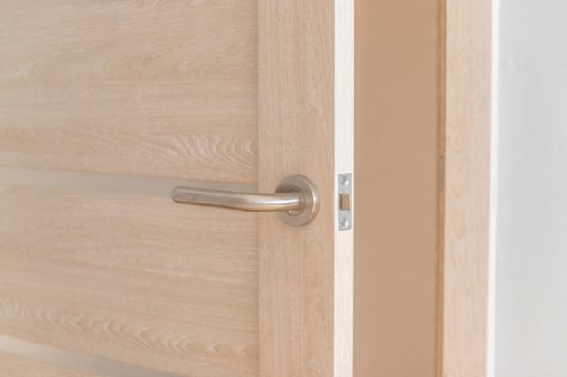 Otwórz jasne drewniane drzwi z zamkiem i metalową klamką w pokoju hotelowym lub hostelowym