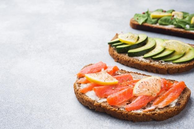 Otwórz kanapki ze szpinakiem i łososiem z awokado na szarym stole. skopiuj miejsce