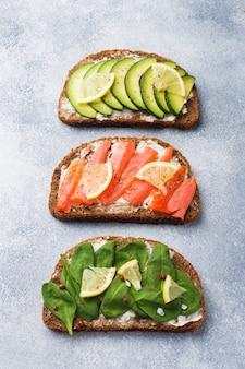 Otwórz kanapki ze szpinakiem i łososiem z awokado na szarym stole.
