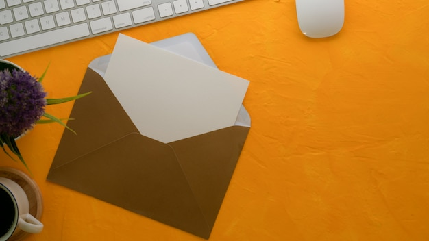 Otwórz kartkę z życzeniami z brązową kopertą na kreatywnym stole roboczym z klawiaturą komputerową, dekoracją i przestrzenią kopii