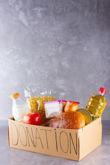Otwórz kartonowe pudełko z olejem, mlekiem, konserwami, makaronem i chlebem. koncepcja darowizny