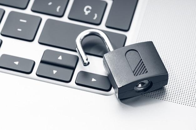Otwórz kłódkę na nowoczesnym laptopie. koncepcja luki w zabezpieczeniach komputera