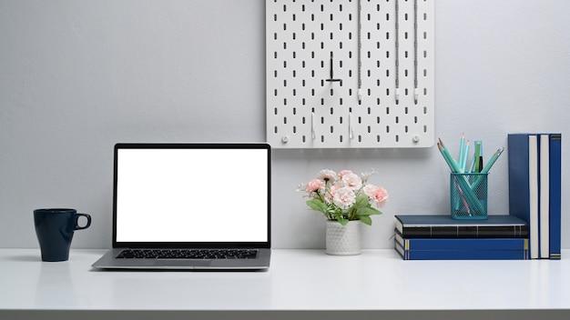 Otwórz komputer przenośny z pustym ekranem na białym stole