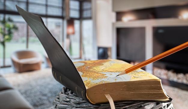Otwórz książkę biblia ołówkiem, na tle salonu. czytanie książki w przytulnym otoczeniu.