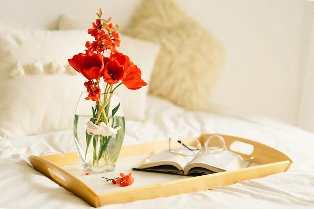 Otwórz książkę i wazon czerwone tulipany na tacy na łóżku
