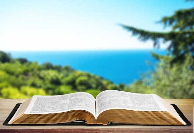 Otwórz książkę na starym drewnianym stole.