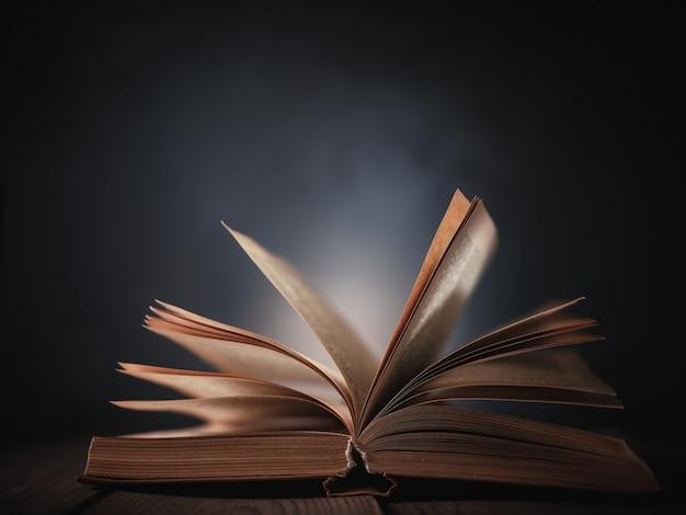 Otwórz książkę na stole na tle ciemnej ściany