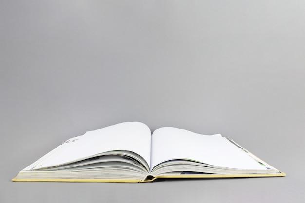 Otwórz książkę na szarym tle. koncepcja wiedzy i edukacji. skopiuj miejsce.