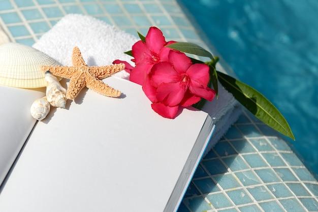 Otwórz książkę z muszli, rozgwiazdy i różowy kwiat