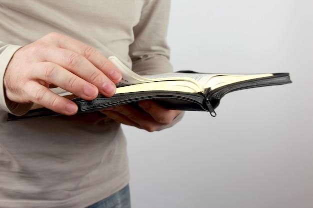 Otwórz księgę biblii w rękach mężczyzn