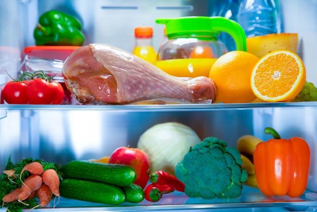 Otwórz lodówkę. udko z indyka świeże warzywa i owoce. świeży sok.