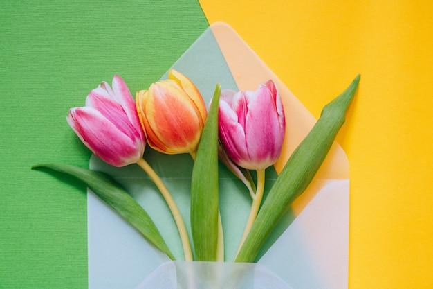 Otwórz matową przezroczystą kopertę z wielobarwnych tulipanów na zielonym i żółtym tle