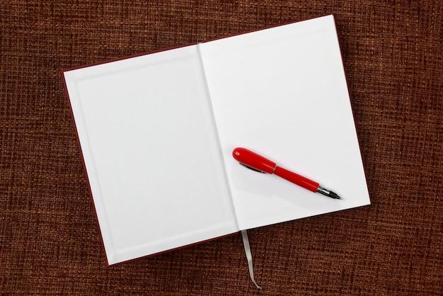 Otwórz notatnik i zbliżenie czerwony długopis