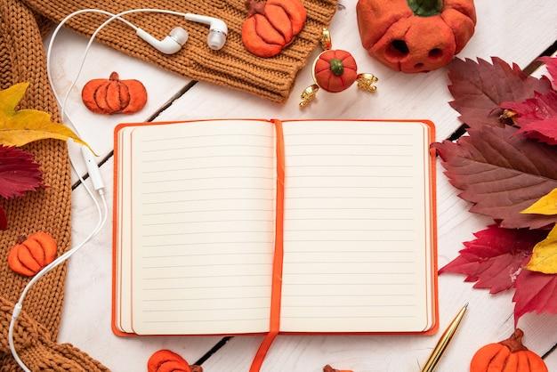 Otwórz notatnik na stole z jesiennymi liśćmi i dynią.