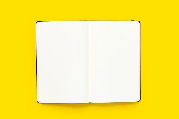 Otwórz notatnik na żółtym tle. widok z góry