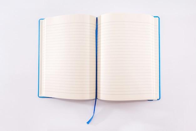 Otwórz notatnik niebieski na białym tle. widok z góry. pusty notatnik. leżał płasko. miejsce na twój tekst.