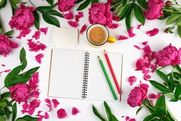 Otwórz notatnik w klatce, drewniane ołówki i żółtą filiżankę kawy