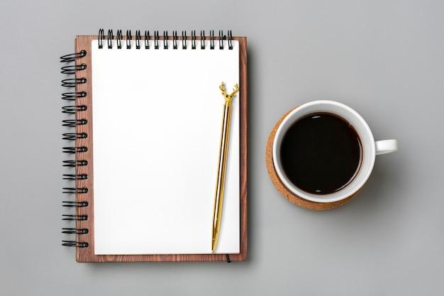 Otwórz notatnik z filiżanką kawy i złotym długopisem