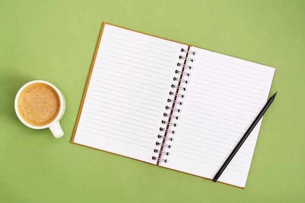 Otwórz notatnik z pustą stroną i filiżanką kawy. blat, miejsce do pracy na zielonym tle. kreatywne mieszkanie leżało.