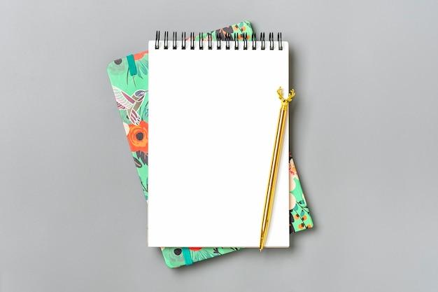 Otwórz notatnik ze złotym długopisem i spiralnym notatnikiem na stole
