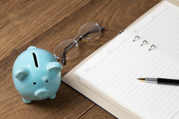 Otwórz pamiętnik na drewnianym stole z piórem, okularami, skarbonką, uwaga na koncepcję oszczędzania pieniędzy