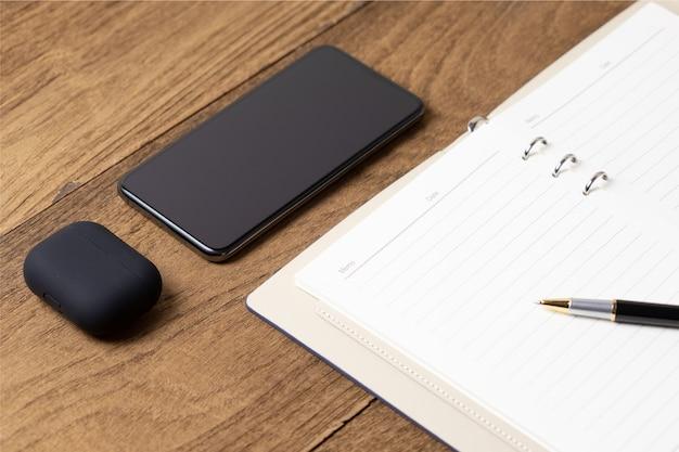 Otwórz pamiętnik na drewnianym stole ze smartfonem, bezprzewodową słuchawką i długopisem na książce