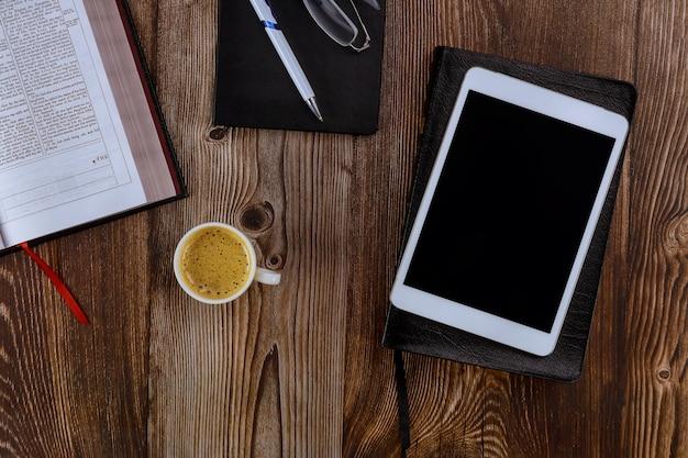 Otwórz pismo święte leżące na drewnianym stole w czytaniu cyfrowego tabletu z filiżanką kawy