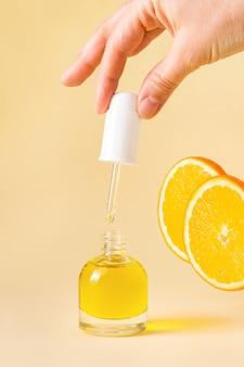 Otwórz pomarańczową butelkę z pipetą w kobiecej dłoni na jasnożółtym tle