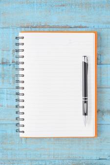 Otwórz pomarańczowy notebook i długopis na niebieskim stole drewna