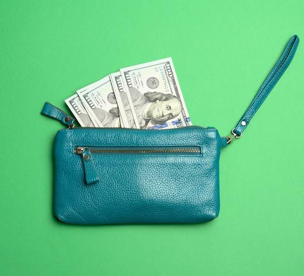 Otwórz portfel z papierowymi banknotami stu dolarowymi na zielono.
