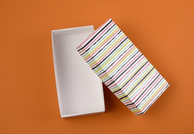 Otwórz prostokątne kartonowe puste pudełko na brązowym tle, widok z góry