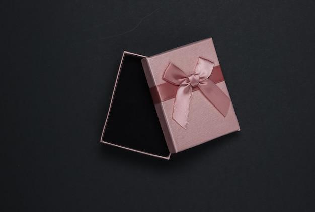 Otwórz pudełko z kokardą na czarnym tle. kompozycja na boże narodzenie, urodziny lub wesele. widok z góry