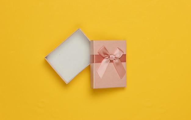 Otwórz pudełko z kokardą na żółtym tle. kompozycja na boże narodzenie, urodziny lub wesele. widok z góry