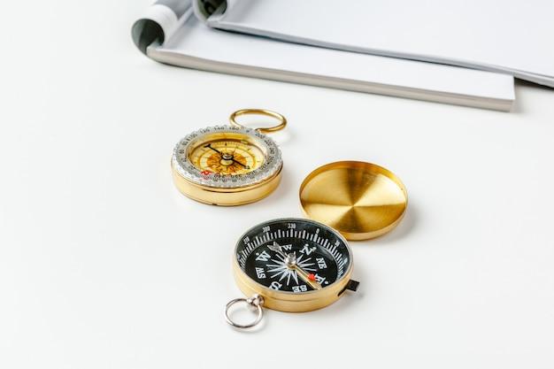 Otwórz pustą stronę magazynu dla miejsca kopiowania ze złotym kompasem na białym stole
