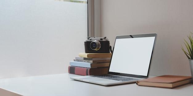 Otwórz pusty ekran laptopa z filiżanką kawy i artykułami biurowymi w wygodnym miejscu pracy
