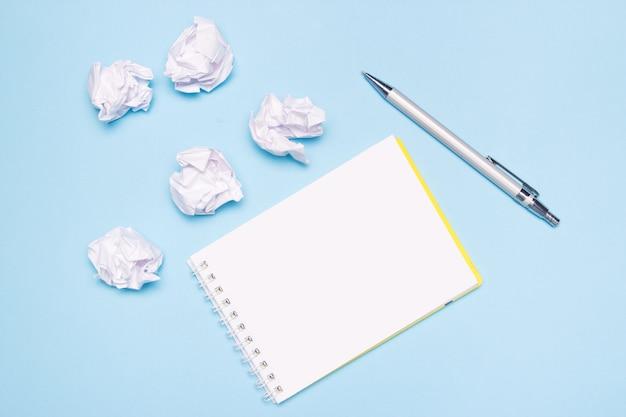 Otwórz pusty notatnik, długopis i zmięte kulki papieru na niebieskim papierze