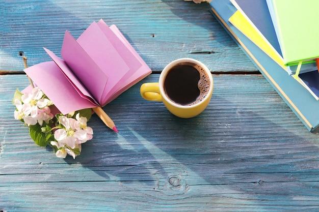 Otwórz pusty notatnik i ołówek, filiżanka kawy, kwiaty na drewnianym stole, wiosna