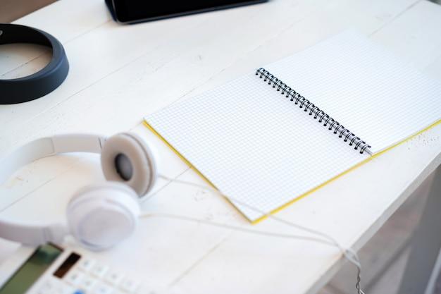 Otwórz pusty notatnik i słuchawki na stole