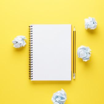 Otwórz pusty notatnik, ołówek i pomięte papiery na żółtym tle. proces twórczy lub próby twórcze.