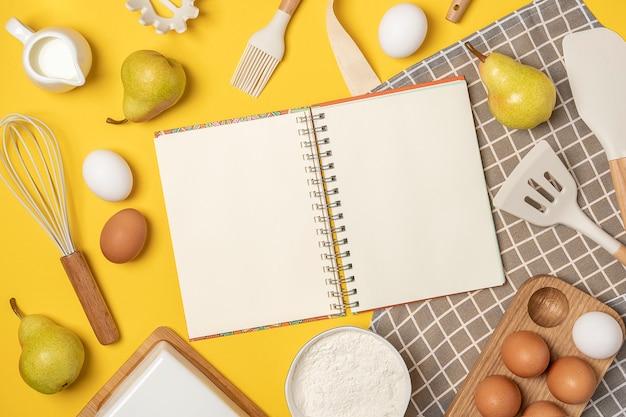 Otwórz pusty notatnik, składniki do pieczenia i naczynia do gotowania, na żółtym tle. szablon przepisów kulinarnych lub projektu. widok z góry płaska makieta świeckich.