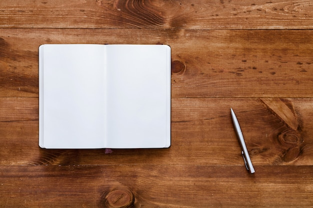 Otwórz pusty notatnik z piórem na brązowym drewnianym biurku