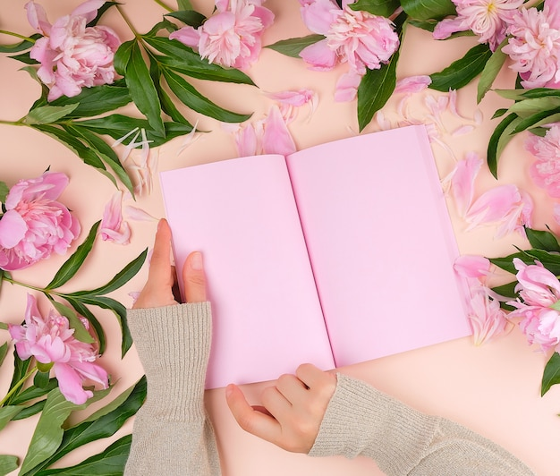 Otwórz pusty notatnik z różowymi prześcieradłami i kwitnącymi piwoniami z zielonymi liśćmi