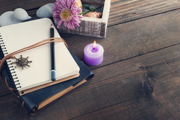 Otwórz pusty notatnik, zapaloną świecę, kwiat