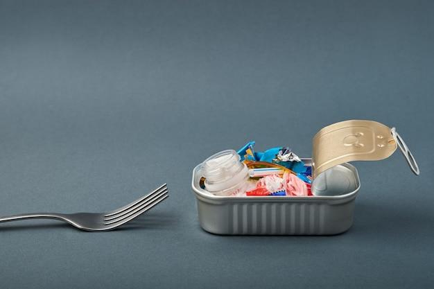 Otwórz puszkę i widelec. odpady z tworzyw sztucznych zamiast ryb w środku.