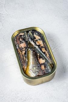 Otwórz puszkę z sardynką w oliwie z oliwek. białe tło. widok z góry.