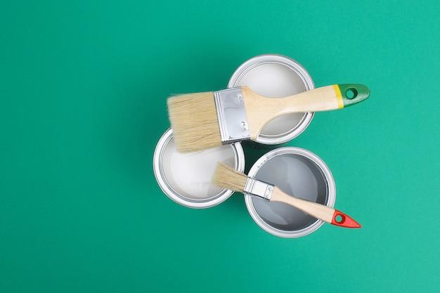 Otwórz puszki po farbie ze szczotkami obok